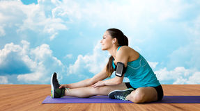 Smiling woman stretching leg on mat over clouds Royalty Free Stock Photos