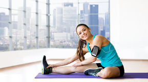 Smiling woman stretching leg on mat over gym Royalty Free Stock Image