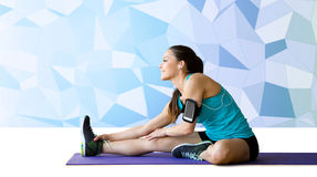 Smiling woman stretching leg on mat over low poly Stock Photos