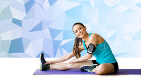 Smiling woman stretching leg on mat over low poly Stock Photo
