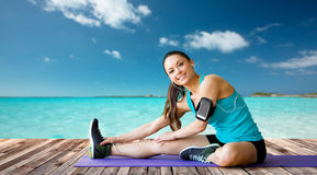 Smiling woman stretching leg on mat over sea Stock Photo