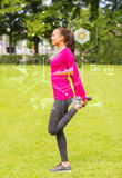 Smiling woman stretching leg outdoors Royalty Free Stock Photography