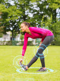 Smiling woman stretching leg outdoors Stock Image