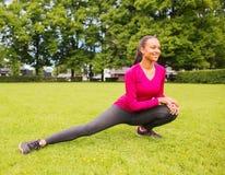 Smiling woman stretching leg outdoors Stock Photos