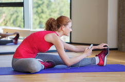 Smiling woman stretching on mat in the gym Stock Photos