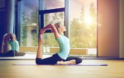 Smiling woman stretching on mat in gym. Fitness, sport, training and lifestyle concept - smiling woman stretching on mat in gym Royalty Free Stock Image