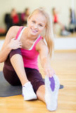 Smiling woman stretching on mat in the gym Royalty Free Stock Photos