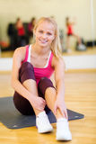 Smiling woman stretching on mat in the gym Stock Images