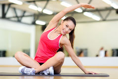 Smiling woman stretching on mat in the gym Royalty Free Stock Photo