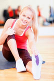 Smiling woman stretching on mat in the gym Royalty Free Stock Images