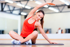 Smiling woman stretching on mat in the gym Stock Photo