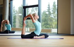 Smiling woman stretching on mat in gym Royalty Free Stock Photo