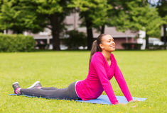 Smiling woman stretching on mat outdoors Royalty Free Stock Image
