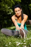 Smiling woman stretching in park Stock Photography