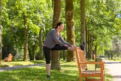 Smiling woman stretching in park on sunny day royalty free stock images