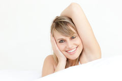 Smiling woman stretching sitting on her bed Royalty Free Stock Images