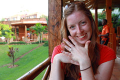 Smiling Woman with String Engagement Ring. A smiling woman sits in a tropical place displaying her simple and cheap engagement ring made out of string Royalty Free Stock Photo