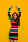 Smiling Woman In Striped Dress With Arms Raised. Happy beautiful young woman in colorful vibrant striped dress with long sleeves is holding arms raised, smiling Stock Photo