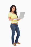 Smiling woman student standing with a laptop. Portrait of a smiling woman student standing with a laptop Royalty Free Stock Image
