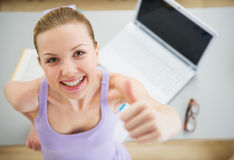 Smiling woman studying in kitchen and showing thumbs up Stock Photos