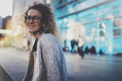 Smiling woman in stylish clothing wearing eye glasses outside in the european night city. Bokeh and flares effect on. Blurred background stock images