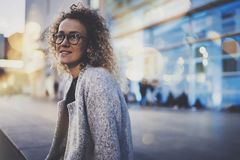 Smiling woman in stylish clothing wearing eye glasses outside in the european night city. Bokeh and flares effect on. Blurred background stock photos