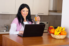 Smiling woman suing laptop in kitchen Stock Photography