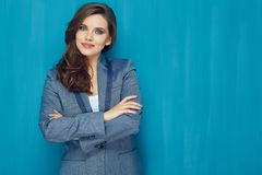 Smiling woman suit dressed standing with crossed arms. Against blue wall back Stock Image