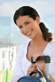 Smiling woman with a suitcase Stock Images