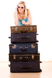 Smiling woman with suitcases. Smiling young woman in sunglasses leaning on pile of packed suitcases, white background Stock Photography