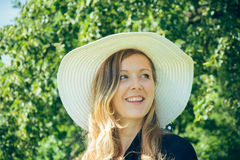 Smiling woman with summer hat. In nature Royalty Free Stock Photos