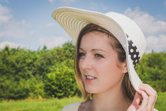 Smiling woman with summer hat. In nature Royalty Free Stock Photography