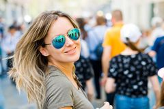 Smiling woman in sun glasses looking back in a city stock photo