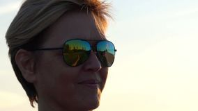 Smiling woman in sun glasses shows two thumb up gestures. An optimistic view of a smiling woman in sun glasses who shows two thumb up gestures at sunset. She stock video