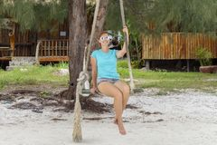 Smiling woman in sunglasses on beach swing. Tropical island vacation relax by sea. White sand beach day activity. Green exotic island shore with wooden huts Royalty Free Stock Images