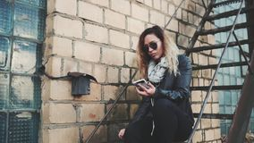 Woman listening to music on the stairs of industrial building. Smiling woman in sunglasses, a black leather jacket, black jeans standing on an urban metal stair stock video