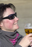 Smiling woman in sunglasses with a glass of beer Stock Photography
