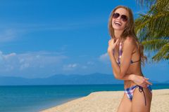 Smiling woman with sunglasses on sandy beach Stock Image