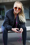Smiling woman with sunglasses sits outdoor and uses phone Stock Photo