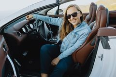 Smiling woman in sunglasses sitting in a car Royalty Free Stock Image