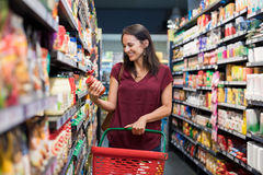 Smiling woman at supermarket. Happy mature woman looking at product at grocery store. Smiling hispanic woman shopping in supermarket and reading product Stock Photo