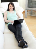 Smiling woman surfing the internet lying on a sofa. At home Royalty Free Stock Image