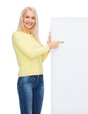 Smiling woman in sweater with blank white board Royalty Free Stock Image