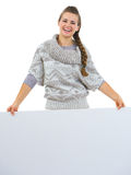 Smiling woman in sweater holding blank billboard Stock Photos