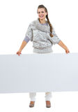 Smiling woman in sweater holding blank billboard Stock Image
