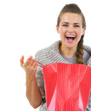 Smiling woman in sweater opening shopping bag Stock Photos