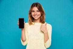 Smiling woman in sweater showing blank smartphone screen. And thumb up while looking at the camera over blue background Stock Images