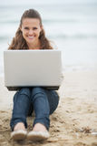 Smiling woman in sweater sitting on beach with laptop Royalty Free Stock Image