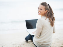 Smiling woman in sweater sitting on beach and using laptop Royalty Free Stock Photo