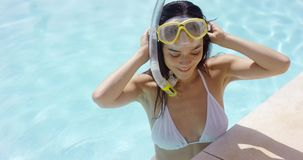 Smiling woman in swim suit wears goggles stock video